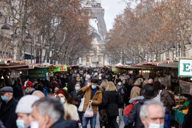 People walk through the streets of Paris.