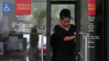 A customer leaves a Wells Fargo Bank branch office July 12