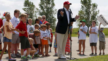 Donald Trump is surrounded by a group of kids.
