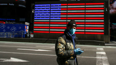 A man wears a face mask as he check his phone in Times Square on March 22, 2020 in New York City. - Coronavirus deaths soared across the United States and Europe on despite heightened restric