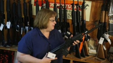 A clerk at Freddie Bear Sports store in Illinois, shows a customer an AK-47 style rifle on Dec. 17.