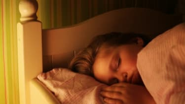 A young girl sleeps with a light on