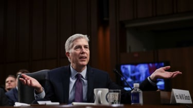 Neil Gorsuch shrugs as he sits in the Senate.