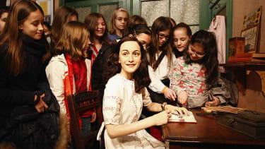 Girls surround a wax figure of Anne Frank
