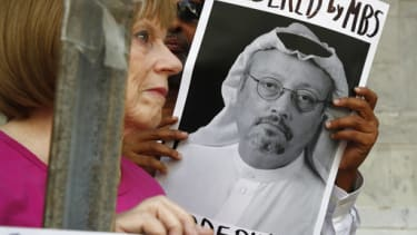 People hold signs during a protest at the Embassy of Saudi Arabia about the disappearance of Saudi journalist Jamal Khashoggi, Wednesday, Oct. 10, 2018, in Washington.