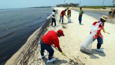 Workers cleanup oil left on the beaches of Waveland, Mississippi.