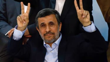 Mahmoud Ahmadinejad raises his hands in V for victory signs