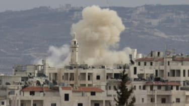 Smoke rises as Idlib city is shelled by Syrian government forces Wednesday.