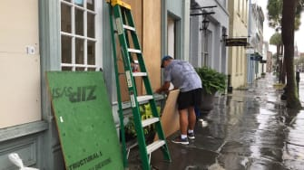 A man boards up his jewelry store in Charleston.