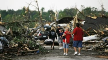 People walk through a demolished neighborhood the day after a deadly tornado ripped through Joplin, Missouri, leaving a path of destruction nearly one mile wide.