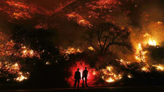 Firefighters look at flames during the 2017 Thomas Fire.