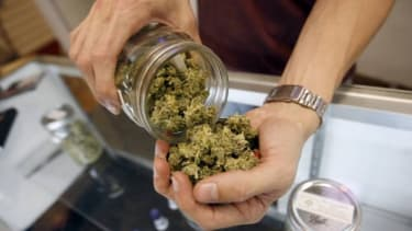 """A """"budtender"""" pours marijuana from a jar at a medical marijuana dispensary in Los Angeles in 2012. Soon, this will all be perfectly legal in Uruguay."""