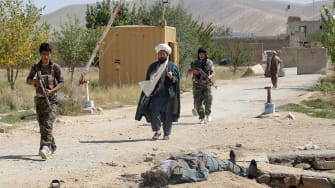 A Taliban insurgent lies dead after an attack on a prison in Ghanzi, Afghanistan