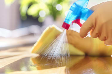 A person sprays a counter with cleaning solution.