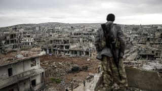 A marksman looks out over a destroyed Syrian city