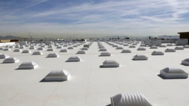 While white roofs, like the one on this Las Vegas Walmart store, help reduce energy use indoors, the effect the white has on global warming is not as obvious.