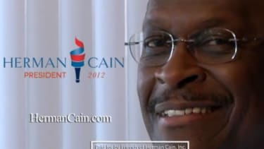 GOP presidential candidate Herman Cain smiles at the end of his latest campaign video, which also features his cigarette-smoking chief of staff and an 80s-esque theme song.
