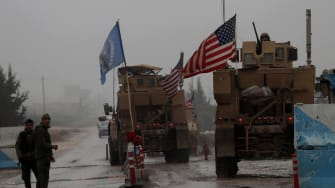 U.S. military vehicles drive through a checkpoint in Syria
