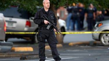 A SWAT team officer stands outside the Aurora, Colo., apartment building where James Holmes, the alleged gunman, was living.