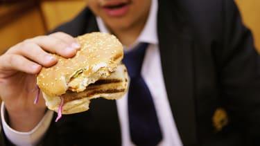 Teen holding hamburger.