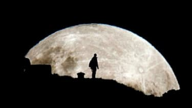 A person is silhouetted against the rising super moon in New Zealand on May 6