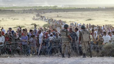 Syrian refugees are held at the border with Turkey.