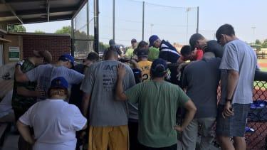 House Democrats praying on baseball field.