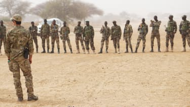 A U.S. Army Special Forces weapons sergeant speaks to a group of Nigerien soldiers before a training exercise.