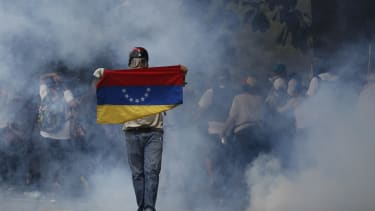 An anti-government protester holds a Venezuelan flag.