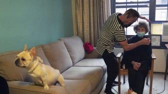 Roberto Novo gives a haircut to an elderly client.