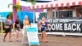 People walk along the Santa Monica Pier.