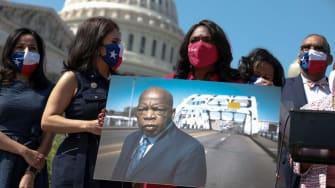 Rep. Terri Sewell holds a photo of the late Rep. John Lewis.
