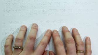 A person reads a book in Braille.