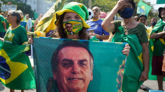 A supporter of Jair Bolsonaro wears a mask with his photo on it.