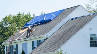 A person fixes a roof.