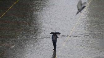 A man with an umbrella walks in the rain.
