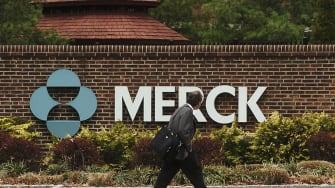 Man walks past Merck plant.