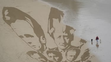 G7 leaders in sand.