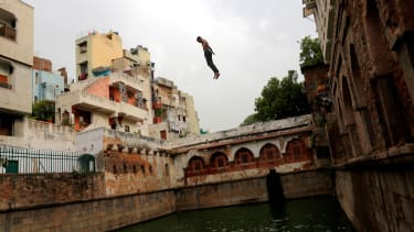 A boy jumping into water.