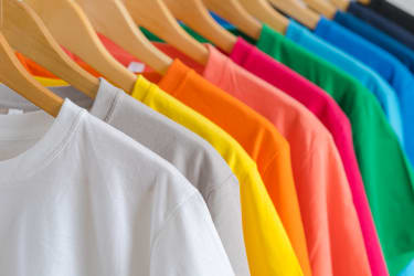 Colorful t-shirts on hangers.