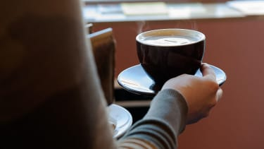 A woman carries a cup of coffee.