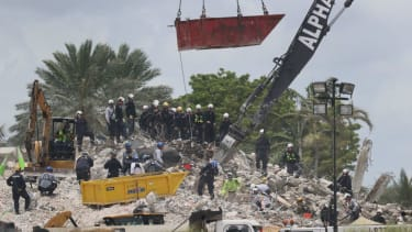 Rescue workers dig through the Champlain Towers South debris pile.