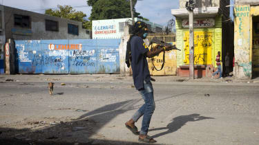 A civilian takes up arms against gang members in Port-au-Prince.