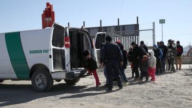 Migrants enter a Border Patrol van.