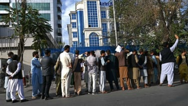 Afghans line up at an ATM machine.