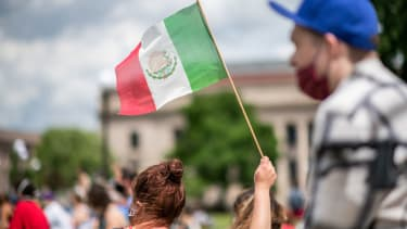 Woman holding Mexican flag.