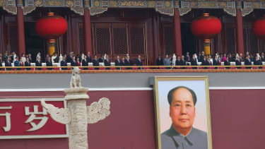 Xi Jinping stands above portrait of Mao Zedong.