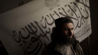 A Taliban official in front of a flag.