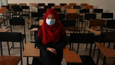An Afghan girl sits in an empty classroom.
